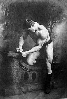 """In Deutschland sind Kettlebells seit dem 19. Jahrhundert bekannt. Die früheren Strongmen haben gerne mit Kugelhanteln trainiert. Einer der bekanntesten Anwender war George Hackenschmidt * 20. Juli 1878; † 19. Februar 1968), alias """"Der russische Löwe"""" (5). (Bildquelle: Wikimedia / Begas. Monumente für das Kaiserreich ; Public Domain Lizenz)"""